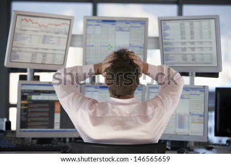 Rear view of stock trader with hands on head looking at multiple computer screens - stock photo