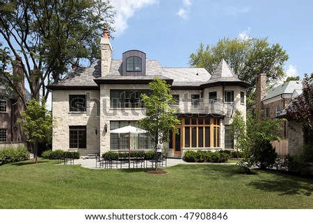 Rear view of stone home with patio - stock photo