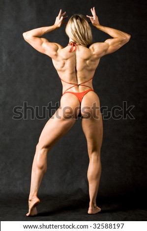 Rear view of strong female in red bikini against black background - stock photo