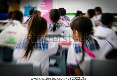 Rear view of student in classroom on blurry