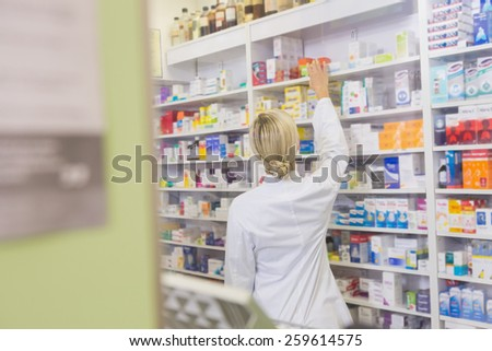 Rear view of student taking medicine from shelf in the pharmacy - stock photo