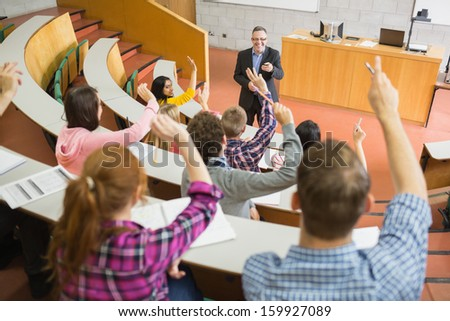 Rear view of students raising hands with a teacher in the college lecture hall - stock photo