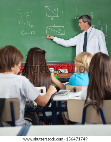 Rear view of students sitting at desk while teacher teaching on board in classroom - stock photo