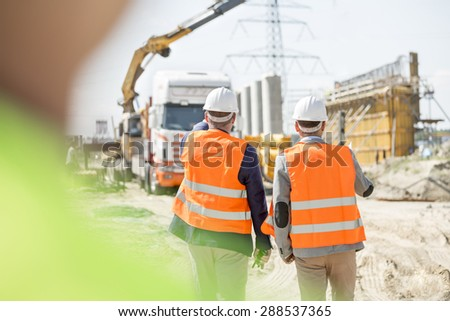 Rear view of supervisors walking at construction site - stock photo