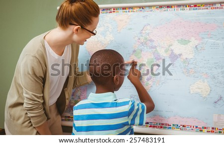 Rear view of teacher assisting little boy to read map in the classroom - stock photo