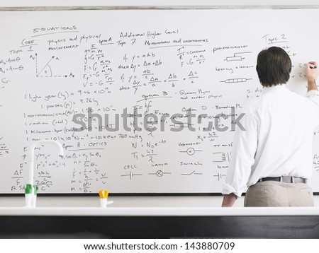Rear view of teacher writing on whiteboard - stock photo