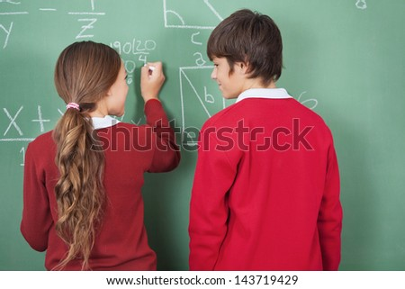 Rear view of teenage students looking each other while solving mathematics on board in classroom