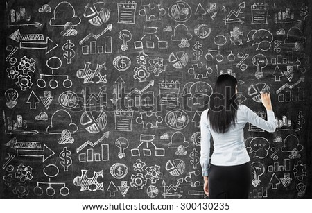 Rear view of the business lady who is drawing business icons on the chalkboard as a wall. - stock photo
