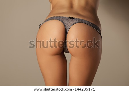 Rear view of the pretty girl buttocks in thong