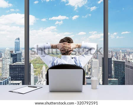 Rear view of the relaxing businessman with crossed hands behind his head, who is looking at the Cntral park. Modern Panoramic office or work place with New York city view. - stock photo