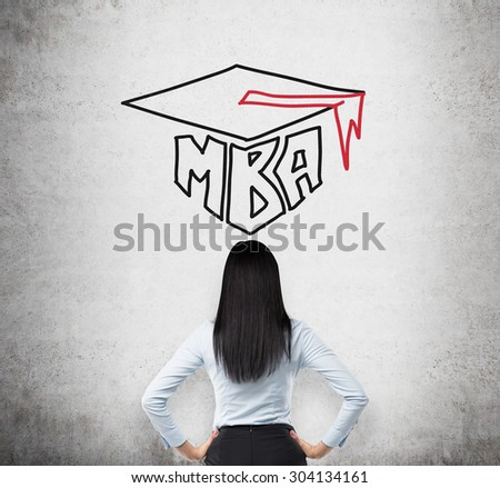 Rear view of the young brunette lady who is thinking about MBA degree. Drawn a graduation hat on the concrete background . - stock photo