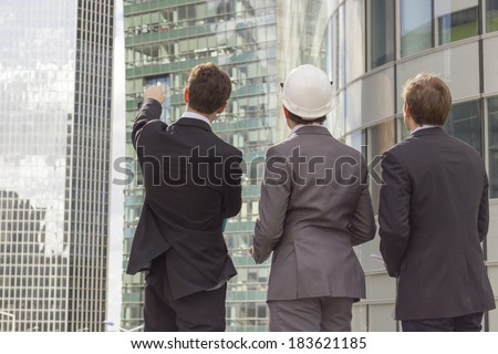 rear view of three architect pointing outside wearing helmet - stock photo