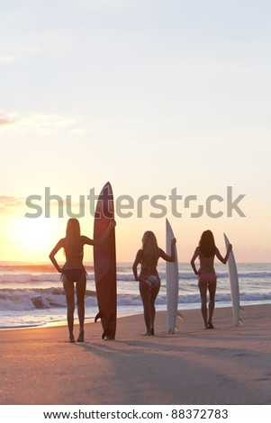 Rear view of three beautiful young women surfer girls in bikinis with surfboards at a beach at sunset or sunrise - stock photo