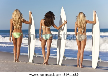 Rear view of three Beautiful young women surfer girls in bikinis with white surfboards at a beach