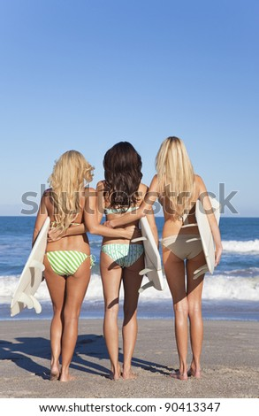 Rear view of three Beautiful young women surfer girls in bikinis with white surfboards at a beach - stock photo