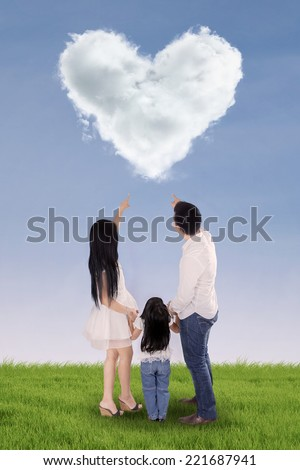 Rear view of three member happy family looking at cloud shaped heart in field