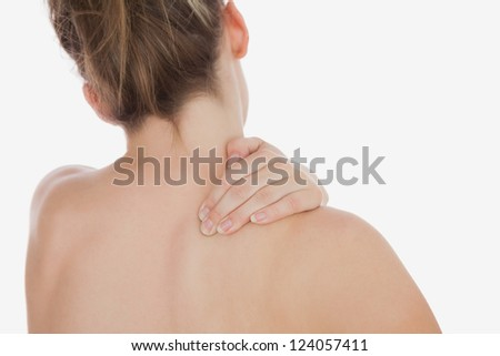 Rear view of topless woman massaging back against white background