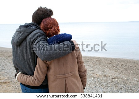 Rear view of tourist couple hugging with heads together on winter beach destination, contemplating the sea on a seasonal holiday, nature outdoors, space. Recreation travel lifestyle, coastal exterior.