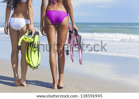 Rear view of two beautiful young women in bikinis with snorkel, mask & flippers on a deserted beach with blue sky - stock photo