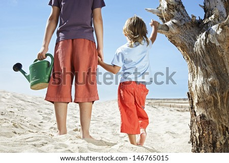 Rear view of two boys with watering can standing by dead tree on beach - stock photo