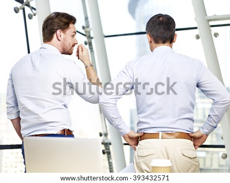 rear view of two caucasian business people looking out of window talking in office. - stock photo