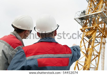 Rear view of two engineer builders at construction site directing to the tower crane