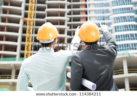 Rear-view of two foremen pointing at the newly-built storey - stock photo