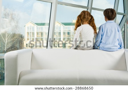 Rear view of two kids sitting on white sofa and looking through window - stock photo