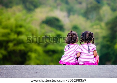 Rear view of two little girl sitting on ground at park - stock photo