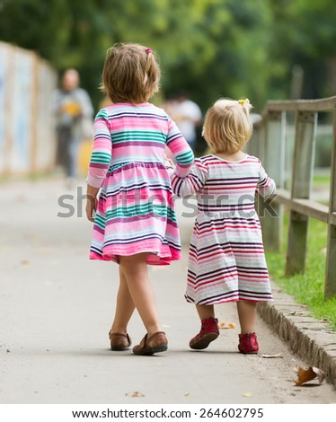 Rear view of two little girls at street in summer - stock photo