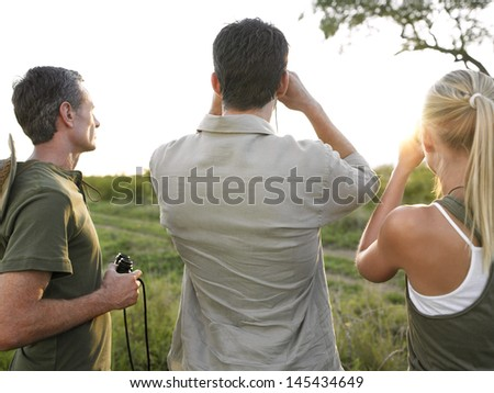 Rear view of two men and woman with binoculars looking at view - stock photo