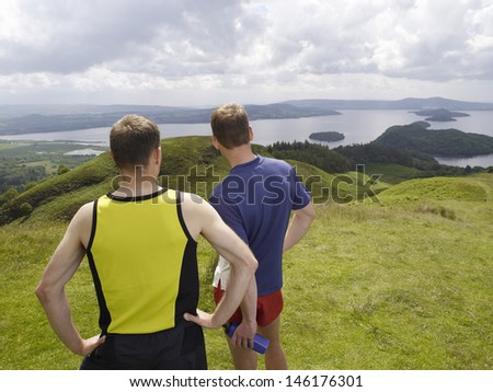 Rear view of two men standing on hill against the lake - stock photo