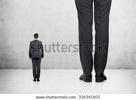 Rear view of two professionals in formal suites who stand in front of concrete wall. - stock photo