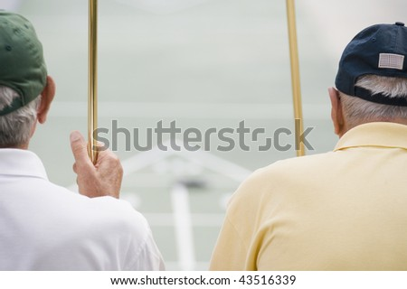 Rear view of two senior men holding shuffleboard cues - stock photo