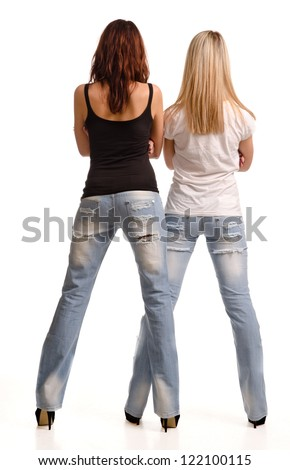 Rear view of two sexy shapely young girls in tight fitting jeans and summer tops standing side by side isolated on white - stock photo