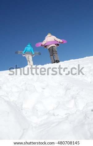 Rear view of two snowboarders climbing on hill