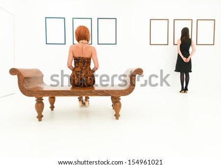 rear view of two women in a white room looking at empty frames displayed on walls in front of them - stock photo