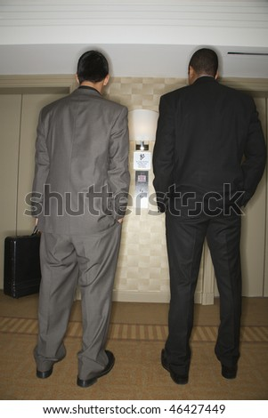 Rear view of two young adult businessmen waiting for an elevator. Vertical format. - stock photo