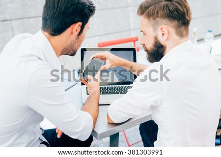 Rear view of two young bearded caucasian modern business man sitting in a bar, using smartphone and laptop, looking downward the screen, smiling - business, work, technology concept