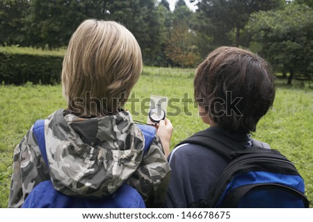 Rear view of two young boys with backpacks using compass - stock photo