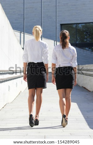 rear view of two young business women walking on street - stock photo