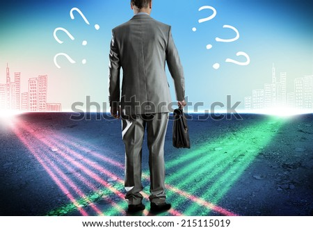 Rear view of uncertain businessman with briefcase - stock photo