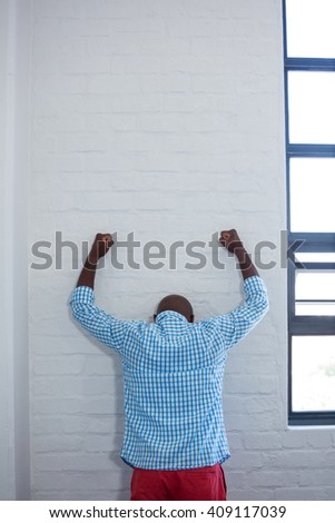 Rear view of upset man leaning against wall in office - stock photo