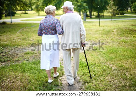 Rear view of well-dressed seniors taking a walk in summer - stock photo