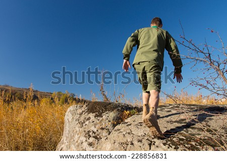 Rear View of White Boy Scout Walking on Old Big Rock at Camp Area on a Blue Sky Background. - stock photo