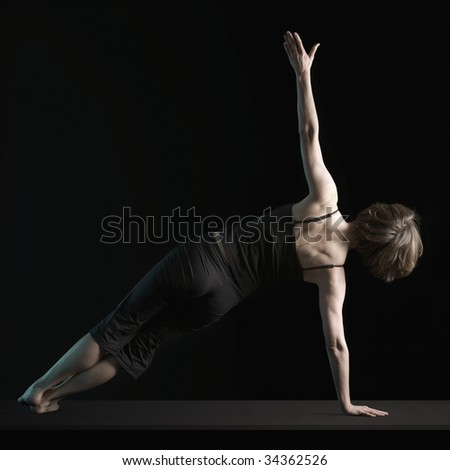 Rear view of woman balanced on one arm in yoga position - stock photo