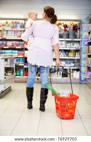 Rear view of woman carrying baby while pulling shopping basket in shopping centre - stock photo