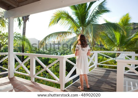 Rear view of woman enjoying the view from a balcony - stock photo