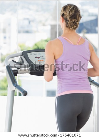 Rear view of woman exercising on treadmill at health club