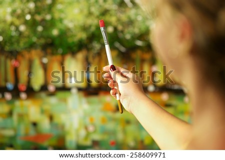 Rear view of woman hand holding painting brush and studying composition of picture on canvas - stock photo